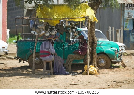 JANUARY 2007 - Old pickup truck and local people sit in shade in the Great Rift Valley, near Nairobi, Kenya, Africa - stock photo
