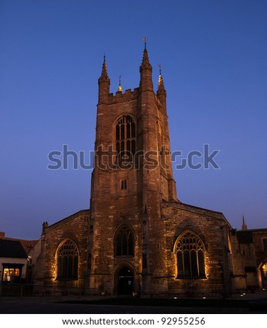 January 2012. The church of St John the Baptist Peterborough, England, UK. Seen at dusk with the walls lit by lighting against a deep blue darkening sky in mid winter. - stock photo