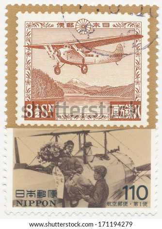 JAPAN - CIRCA  1995: A stamp printed in Japan shows First Osaka-Tokyo airmail flight and workers loading freight onto airplane, Postal History Series, circa 1995