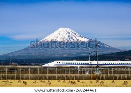 JAPAN - DECEMBER 14, 2012: A Shinkansen bullet train passes below Mt. Fuji in Japan. - stock photo