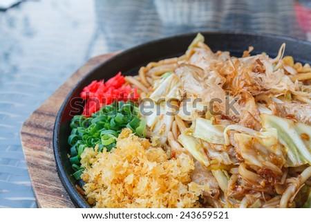 Japan Food: Yakisoba with pork on black plant in restaurant. - stock photo