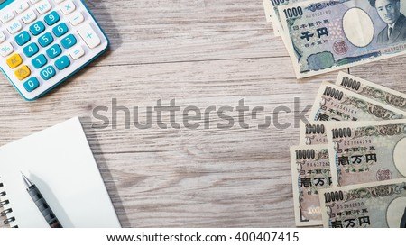 Japan money - Japanese yen currency and Calculator, notebook, pencil on wooden background ( Space and composition for text ) - stock photo