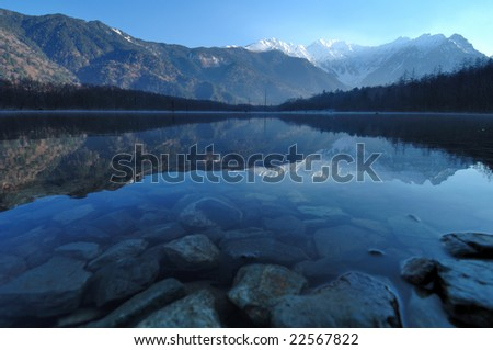 Japanese Alpine Mt. Hotaka mountain range and the virtual image that were reflected in the surface of a lake - stock photo
