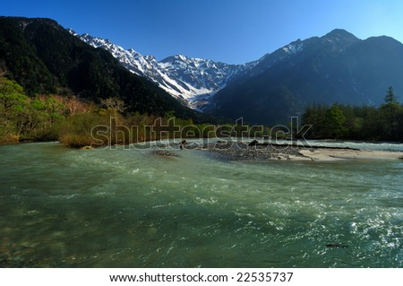 Japanese Alpine remaining snow and the fresh green and Azusa River - stock photo