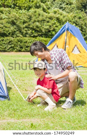 Japanese Boy putting up a tent with his father