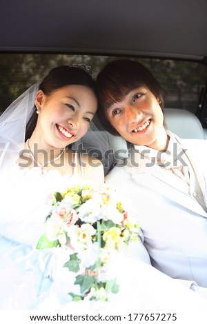 Japanese bride and the groom face-to-face in the car - stock photo