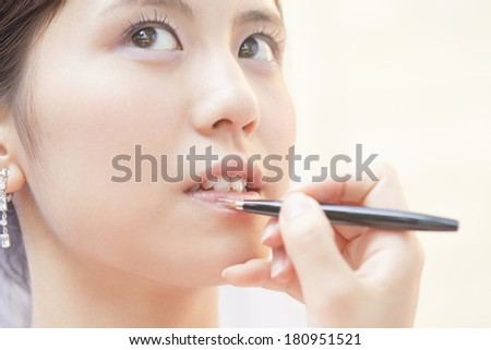 Japanese bride putting on lipstick