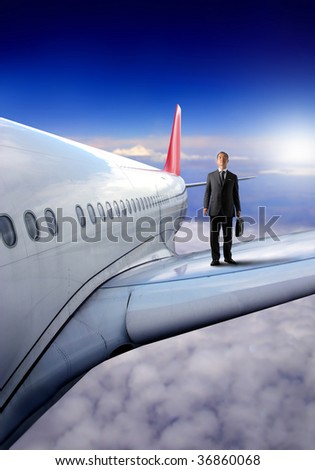 japanese business man on a wing of airplane - stock photo