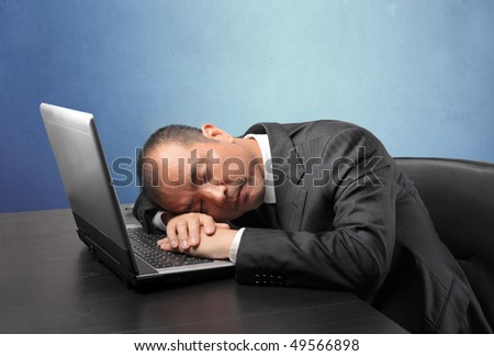 Japanese businessman asleep on a laptop - stock photo