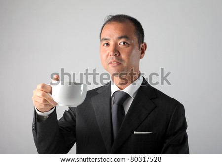 Japanese businessman having a cup of coffee - stock photo