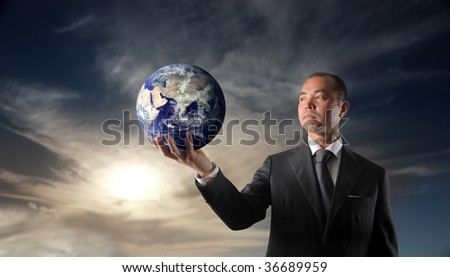 japanese businessman holding planet earth - stock photo