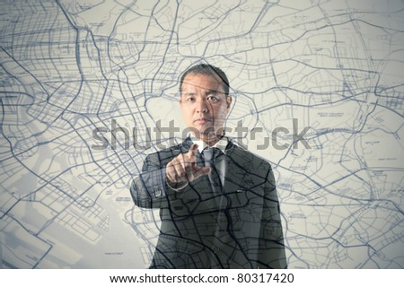 Japanese businessman indicating a route on a city map - stock photo