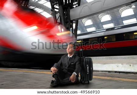 Japanese businessman sitting against a suitcase in a train station - stock photo
