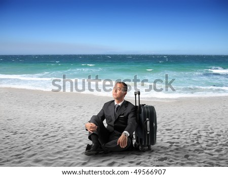 Japanese businessman sitting against a suitcase on a beach - stock photo