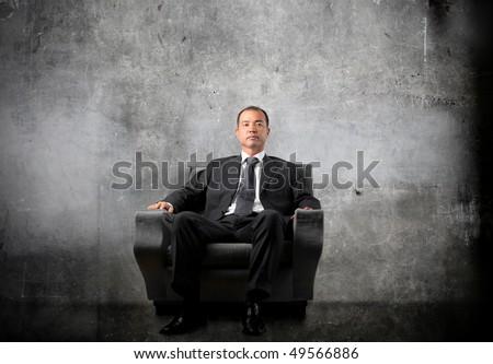 Japanese businessman sitting on an armchair - stock photo
