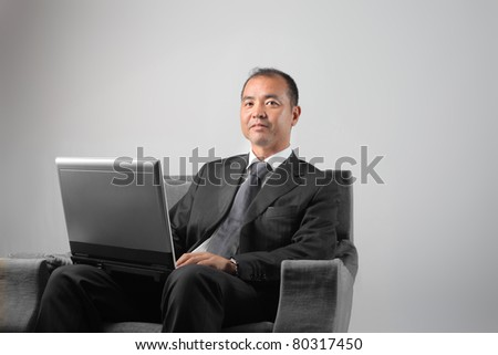 Japanese businessman sitting on an armchair and using a laptop - stock photo
