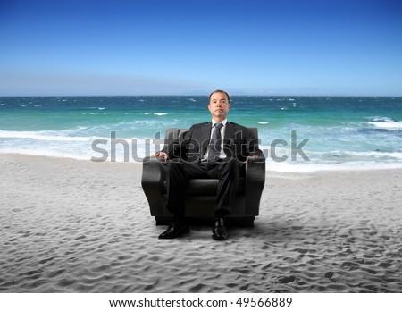 Japanese businessman sitting on an armchair at the beach - stock photo