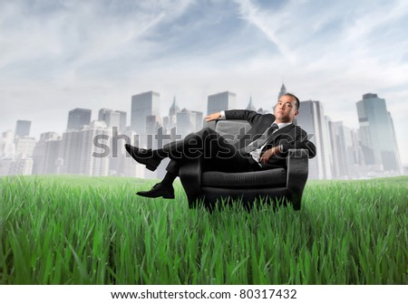Japanese businessman sitting on an armchair on a green meadow with cityscape in the background - stock photo
