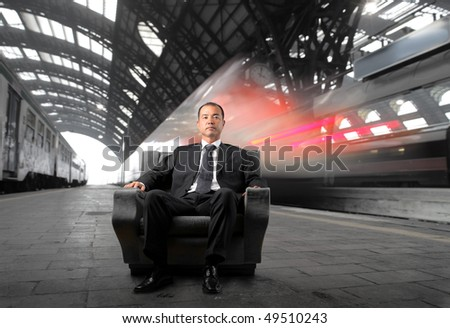 Japanese businessman sitting on an armchair with a train station on the background - stock photo