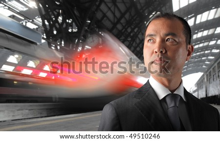 Japanese Businessman standing on the platform of a train station - stock photo