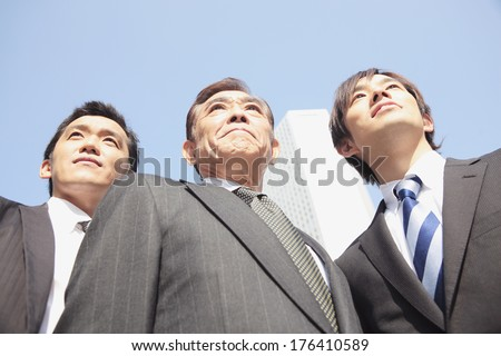 Japanese businessman standing on the street looking ahead - stock photo
