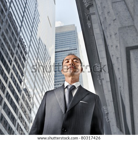 Japanese businessman with modern skyscrapers in the background - stock photo