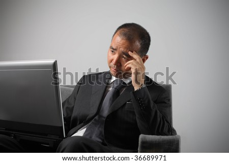 japanese businessman with sad expression working with laptop - stock photo