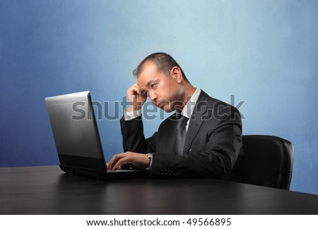 Japanese businessman working on a laptop - stock photo