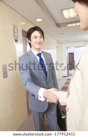 Japanese businesswoman and businessman shaking hands in the corridor