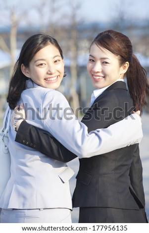 Japanese businesswomen turning around while snuggling - stock photo