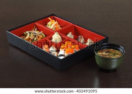 Japanese cafe lunch of sushi, miso soup, gyoza, tuna, ginger, red caviar, wasabi, the pieces of meat, sashimi and salad. Container with compartments for dishes on a wooden table.  - stock photo