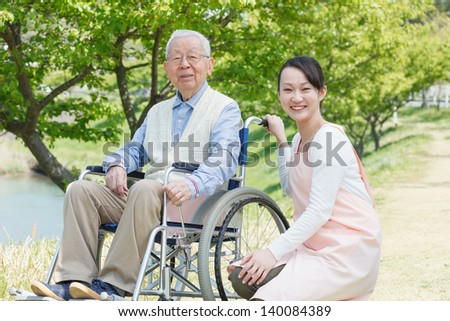 Japanese caregivers and senior smile in the field - stock photo