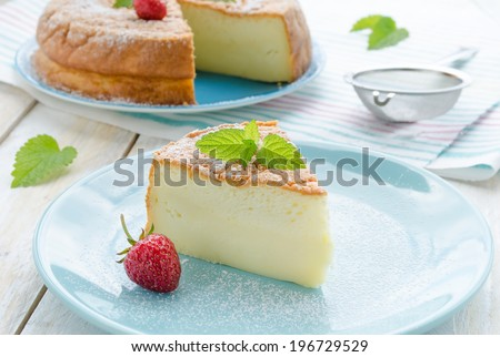 Japanese cheesecake decorated with mint, icing sugar and strawberry - stock photo