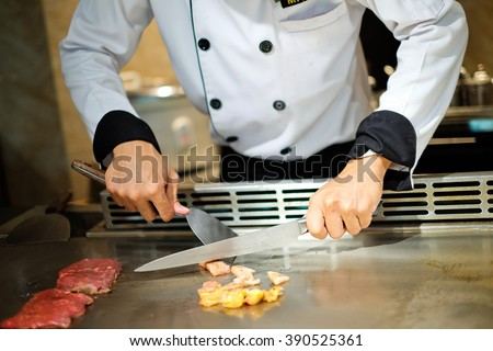 Japanese chef deliberately preparing and cooking traditional beef teppanyaki on a hot plate - stock photo