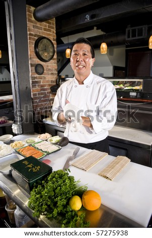 Japanese chef in restaurant with sushi ingredients ready to prepare rolls - stock photo