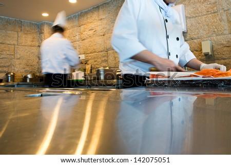 Japanese chef making sashimi in kitchen - stock photo