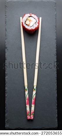 Japanese chopsticks and sushi on a dark background - stock photo