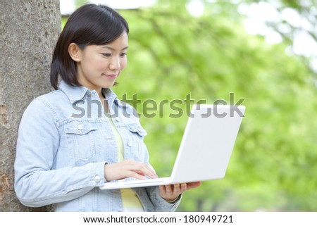 Japanese College students using laptops while leaning on a tree, - stock photo