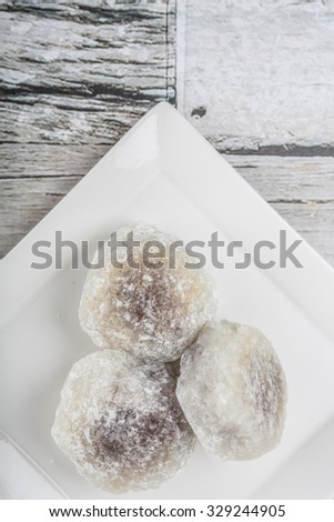 Japanese confection, round glutinous rice stuffed with sweetened red bean paste or locally known as daifukumochi in a white plate over wooden background