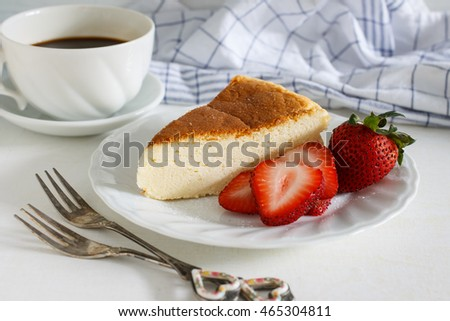 Japanese cotton cheesecake with strawberry on white plates served with hot black coffee.
