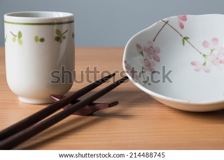 Japanese crockery and chopsticks on a wooden table. - stock photo
