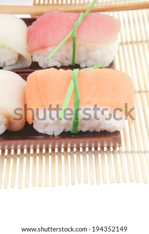 Japanese Cuisine - Different Types of Nigiri Sushi : Tuna (maguro) Salmon (sake) and Eel (unagi) with Wasabi and Ginger on bamboo mat isolated over white background - stock photo