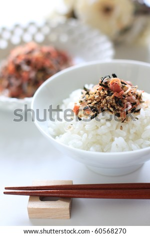 Japanese cuisine, Dried plum and small fishes on rice - stock photo