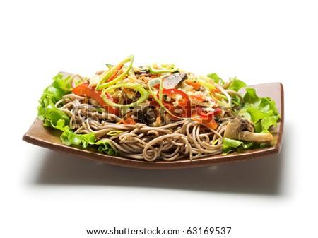 Japanese Cuisine - Fried Noodles with Vegetables and Eggs. Garnished on Salad Leaf - stock photo