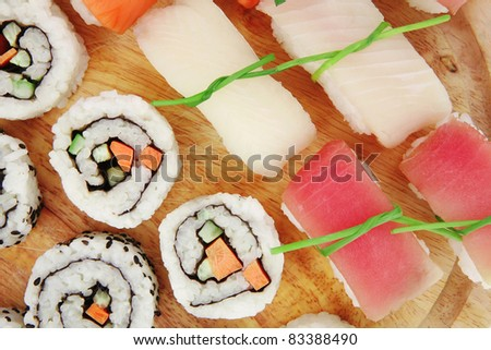 Japanese Cuisine - Maki Roll with Deep Fried Vegetables inside with Set of Nigiri sushi topped with raw Salmon Tuna and Eel. on wooden board . isolated over white background - stock photo