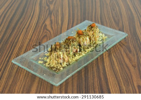 Japanese cuisine of baked salmon maki sushi topped with processed seaweed, roasted same seed and salmon roe. - stock photo