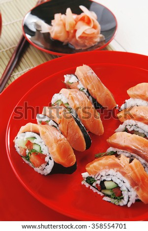 japanese cuisine onigiri sashimi inside out sushi rolls with ginger and sake cup on red plate over white wooden table - stock photo