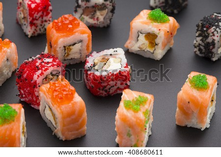 Japanese cuisine. Set of sushi mix roll with different fresh ingredients over black background ( table ).