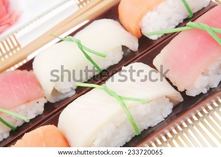 Japanese Cuisine - Set of Tuna (maguro) Salmon (sake) and Eel (unagi) Nigiri Sushi  with Wasabi and Ginger on bamboo mat isolated over white background - stock photo
