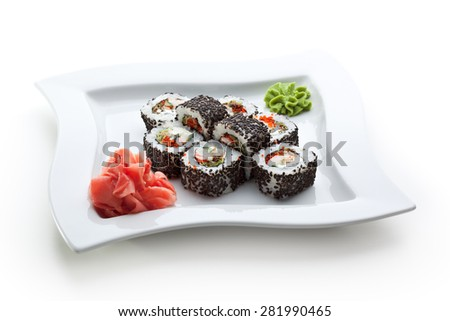 Japanese Cuisine - Sushi Roll with Shrimps, Eel, Salad Leaf, Cream Cheese and Tobiko inside. Sesame outside - stock photo